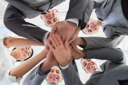 Photo for Business team standing hands together in the office - Royalty Free Image