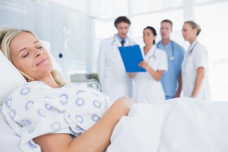 Foto de Sleeping patient with doctors behind in hospital room - Imagen libre de derechos