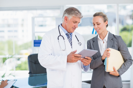 Photo for Confident doctor and pretty businesswoman discussing in medical office - Royalty Free Image