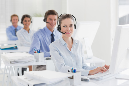 Photo pour Business team working on computers and wearing headsets in call center - image libre de droit