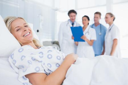 Foto de Smiling patient looking at camera with doctors behind in hospital room - Imagen libre de derechos