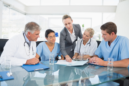 Foto de Team of doctors and businesswoman having a meeting in medical office - Imagen libre de derechos