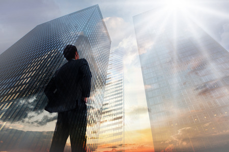 Photo pour Businessman standing with hands on hips against low angle view of skyscrapers at sunset - image libre de droit