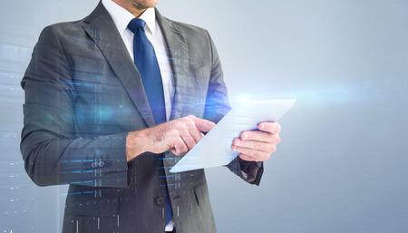 Foto de Businessman using his tablet pc  against grey vignette - Imagen libre de derechos