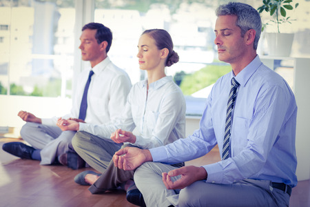 Photo for Business people doing yoga on floor in office - Royalty Free Image