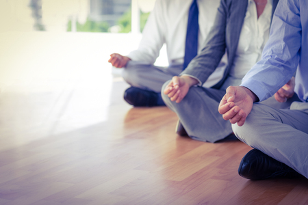 Photo for Close up view of business people doing yoga in office - Royalty Free Image