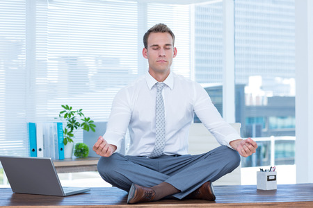 Foto per Zen businessman doing yoga meditation on the desk - Immagine Royalty Free