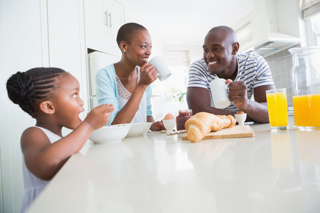 Photo for Happy family sitting and taking breakfast in the kitchen - Royalty Free Image