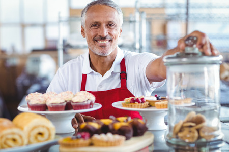 Photo for Happy barista smiling at camera behind plates of cakes in the bakery - Royalty Free Image