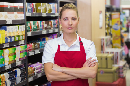 Photo for Portrait of serious blonde worker with arms crossed in supermarket - Royalty Free Image