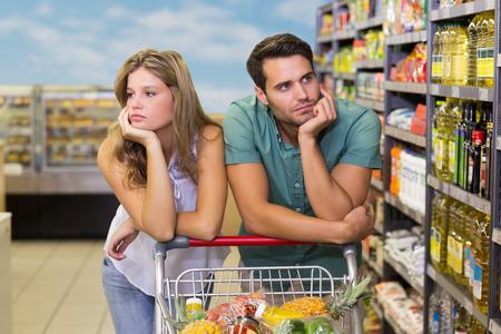 Foto de Serious bright couple buying food products at supermarket - Imagen libre de derechos