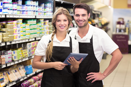 Photo pour Portrait of smiling colleagues using a digital tablet at supermarket - image libre de droit