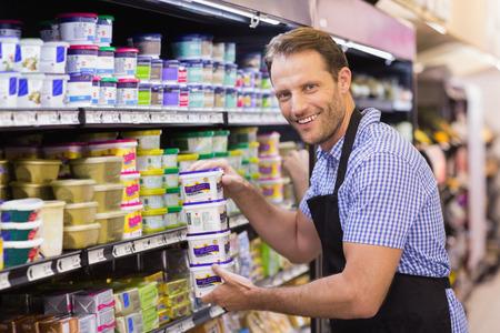 Photo pour Portraits of a smiling handsome holding a dairy products in supermarket - image libre de droit