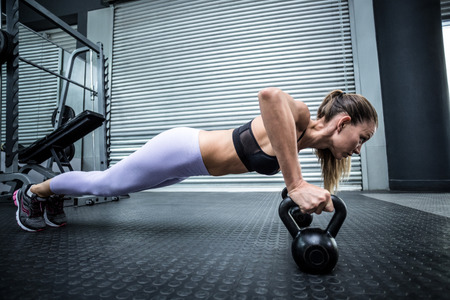 Photo for Side view of a woman doing pushups with kettlebells - Royalty Free Image