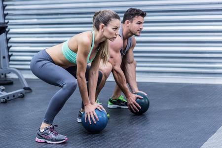 Photo pour Squatting muscular couple doing ball exercise - image libre de droit