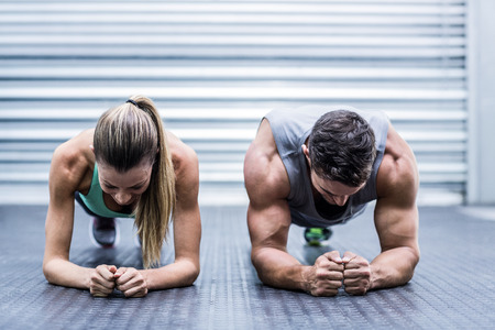 Photo pour Front view of a muscular couple doing planking exercises - image libre de droit