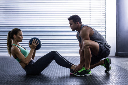 Photo pour Side view of a muscular couple doing abdominal ball exercise - image libre de droit