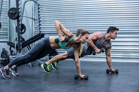 Foto de Muscular couple doing plank exercise while lifting weights - Imagen libre de derechos