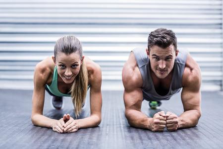 Photo pour Portrait of a muscular couple doing planking exercises - image libre de droit
