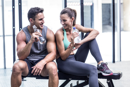 Foto de Muscular couple discussing on the bench and holding water bottle - Imagen libre de derechos