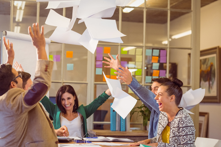 Photo for Group of business people celebrating by throwing their business papers in the air - Royalty Free Image