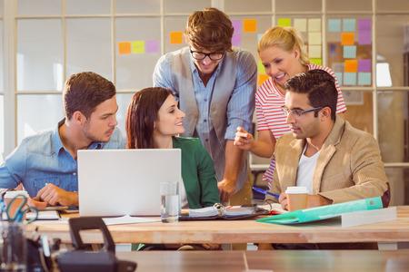 Foto de Happy creative business team using laptop in meeting at office - Imagen libre de derechos