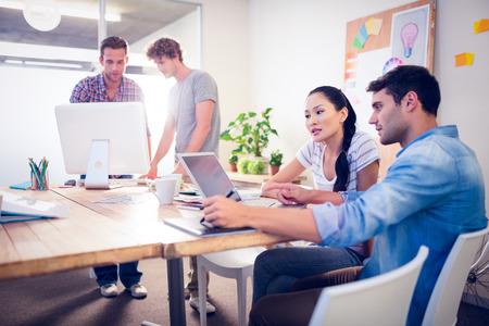 Foto de Creative business team gathered around laptops in the office - Imagen libre de derechos