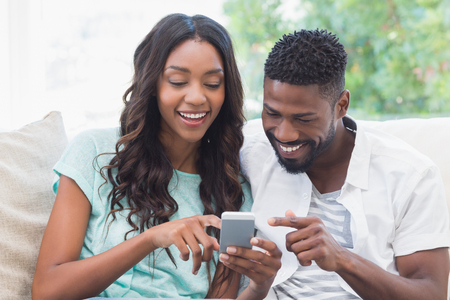 Photo for Happy couple on the couch using phone at home in the living room - Royalty Free Image
