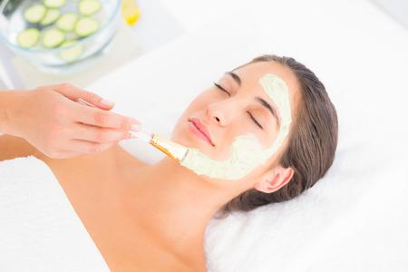 Photo pour Beautiful brunette getting a facial treatment at the health spa - image libre de droit
