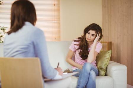 Foto de Therapist listening to her patient in therapists office - Imagen libre de derechos