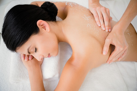 Woman enjoying a salt scrub massage at the health spa