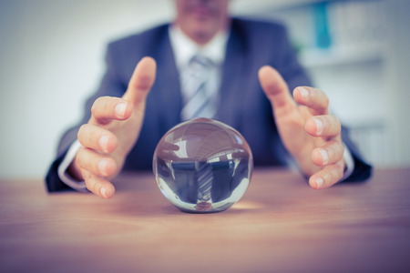 Photo pour Businessman forecasting a crystal ball in the office - image libre de droit