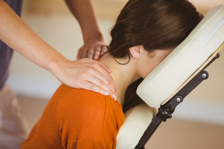 Foto de Young woman getting massage in chair in therapy room - Imagen libre de derechos