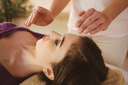 Foto de Young woman having a reiki treatment in therapy room - Imagen libre de derechos