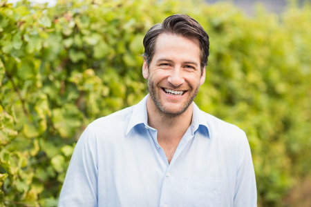 Photo for Young happy man smiling at camera in the grape fields - Royalty Free Image