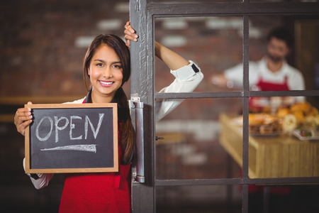 Photo for Portrait of waitress showing chalkboard with open sign at coffee shop - Royalty Free Image