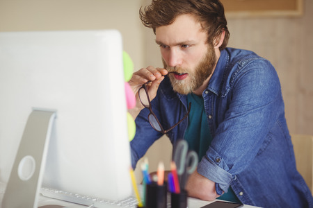 Foto de Focused hipster working at his desk in his office - Imagen libre de derechos