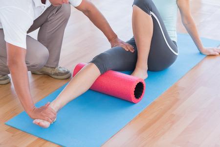 Foto de Trainer working with woman on exercise mat in fitness studio - Imagen libre de derechos