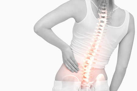 Foto de Digital composite of Highlighted spine of woman with back pain - Imagen libre de derechos