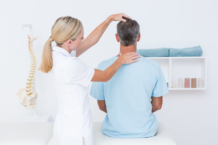 Foto de Doctor doing neck adjustment in medical office - Imagen libre de derechos