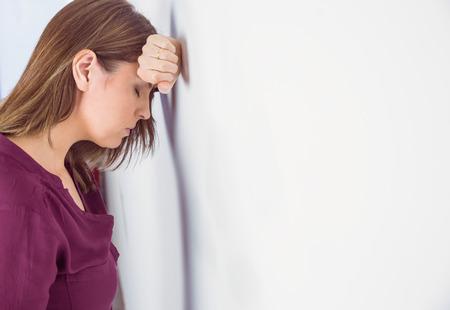 Foto de Depressed woman leaning her head against a wall on white background - Imagen libre de derechos