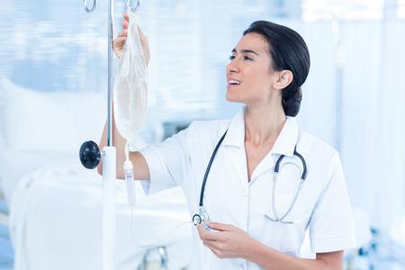 Foto de Nurse connecting an intravenous drip in hospital room - Imagen libre de derechos