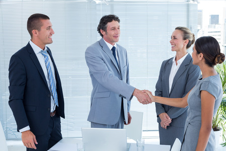 Photo pour Business colleagues shaking hands in the office - image libre de droit