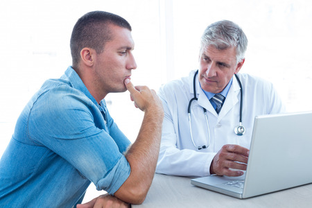 Photo pour Worried patient with his doctor in medical office - image libre de droit