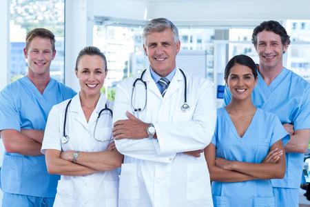 Foto de Team of doctors standing arms crossed and smiling at camera in medical office - Imagen libre de derechos