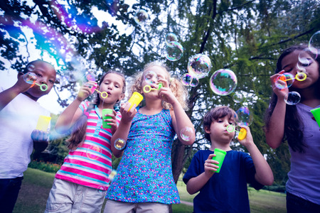 Photo pour Children playing with bubble wand in the park on a sunny day - image libre de droit