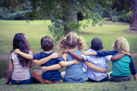 Photo for Back turned sitting children in the park on a sunny day - Royalty Free Image