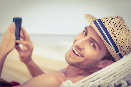 Photo pour Handsome man texting on the hammock on the beach - image libre de droit