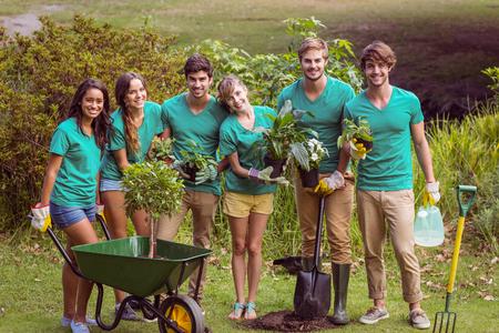 Foto de Happy friends gardening for the community on a sunny day - Imagen libre de derechos