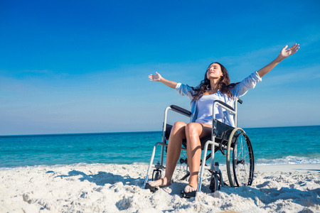 Foto de Disabled woman with arms outstretched at the beach on a sunny day - Imagen libre de derechos